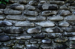 Wall made of stone. Part of the wall of a dark, rough stone Stock Photography