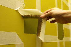 Wall with masking tape. Man removing masking tape from painting wall Royalty Free Stock Photography