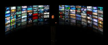 Wall of media screens. Man viewing video displays. Human elements were created with 3D software and are not from any actual human likenesses Stock Image
