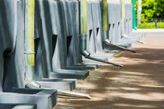 Metal downspouts rain gutter goes on the sidewalk royalty free stock image