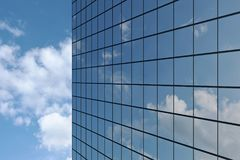 Wall of skyscraper under blue sky with clouds. Wall of modern business skyscraper with blue windows in day sunlight under blue sky with clouds raising to the sky Stock Images
