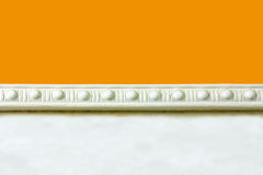 Plaster wall molding. A background of a yellow wall with a plaster border molding royalty free stock photo