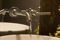 Wall mounted faucet. Close up shot of a wall mounted faucet with water flowing Royalty Free Stock Images