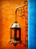 Wall mounted light with ornaments. Vertical shot of ornate wall lantern mounted on a blue wall against an orange background royalty free stock photos