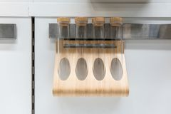 Wall mounted magnetic wooden rack for spice or seasoning tube bo. Ttle in modern kitchen Stock Images