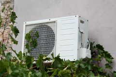 Wall mounted outside air conditioner AC unit mounted on cracked back wall with stone tiles part of family house in front of dense. Garden vine plants on warm royalty free stock photos