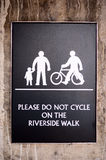 Wall mounted warning sign in London England. This is an image of a wall mounted warning sign advising not to ride a bicycle onthe riverside walk - along the stock images