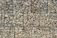 The wall of multi-colored stones covered with iron mesh royalty free stock images