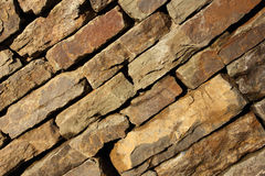 Wall of natural stone on the diagonal. Orange and brown Royalty Free Stock Photos