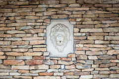 Wall of natural stones with bas-relief of lion Royalty Free Stock Photo