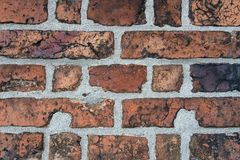 Wall of old cracked red brick with black inclusions.  stock image