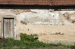 The wall of an old house with a door. The cracked wall of an old house with a door Royalty Free Stock Photos