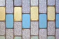 Wall with old plastic tiles of various colors Stock Images