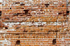 Wall of old red brick with remains of light-coloured plaster Stock Image