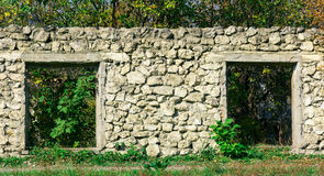 The Wall Of The Old Ruined Building Is Built Of Stone. Overgrown With Shrubs And Trees Royalty Free Stock Photo