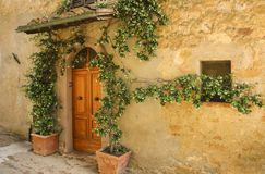 Wall of an old stone house decorated with flowers, Italy stock photography