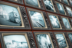 Wall of old TV screens. Creative abstract television broadcasting, news media, business, entertainment and cinema concept: wall of old wooden black and white TV Stock Images