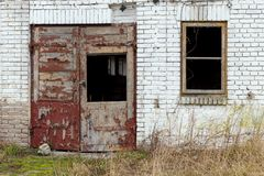 A wall with an old window and a door.  Stock Image