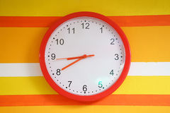 Wall orange clock on colorful. Wall. white watch Stock Photo