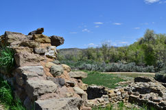 Wall Overlooking Green Field at Aztec Ruins. Ancient wall overlooking a green filed at Aztec Ruins National Monument, a World Heritage Site on a beautiful sunny Stock Image