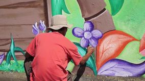 Mural painter draws flowers on concrete wall.