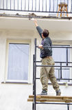Wall painting. A worker on a scaffolding, painting a white wall Stock Photos
