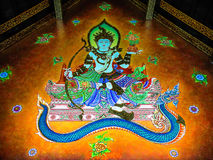 Wall Painting of God Sitting over Snake. Wall painting of a god sitting over a snake at city pillar shrine of Chiangmai province, Thailand Stock Photo