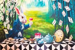 Wall painting of a white rabbit is having a tea party. Bangkok, Thailand - August 12, 2015 : A photo of Alice`s Adventures in Wonderland theme wall painting stock image