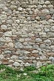 Wall of pale natural stones. Weathered, old stone wall with wild plants in the foreground stock images