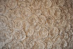 Wall paper flowers - roses in the background. Background with paper flowers - rose, made of Kraft paper Royalty Free Stock Image