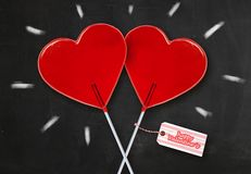 Wall paper Valentines day greeting card with couple of red heart shape lollipops together isolated on blackboard with chalk sparks. Celebrating romantic holiday stock photos