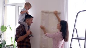 Wall papers for home, beautiful mum and Dad with child on shoulders make repairs in home. Wall papers for renovation home, beautiful mum and Dad with child on stock footage