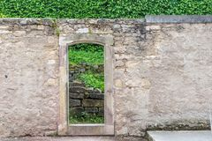 Passage and green hedge. Wall in the park with passage and green hedge in the background royalty free stock photo