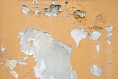 A wall with peeling orange color stock image
