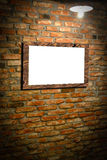 Wall with photo frame. Wooden photo frame on old brick wall with light on stock photo