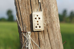 Wall plug on wooden pole Royalty Free Stock Photo