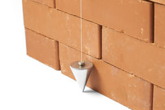 Wall and Plumb Bob. Bricks in masonry with touched plum bob for vertical line isolated on white background Stock Photo