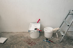 Wall prepared for painting. Brushes, buckets of paint, stairs near the wall Stock Images