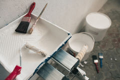 Wall prepared for painting. Brushes, buckets of paint, stairs near the wall Royalty Free Stock Photos
