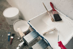 Wall prepared for painting. Brushes, buckets of paint, stairs near the wall Royalty Free Stock Photo