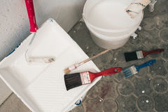 Wall prepared for painting. Brushes, buckets of paint, stairs near the wall Stock Photography