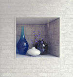 Wall recess with glassware and ceramics. Rectangular wall recess with hand blown blue glassware and ceramics in a textured white brick wall in a luxury house Royalty Free Stock Photo