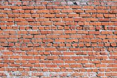 Wall of red brick. The bricks cracked. Masonry is uneven. Wall of red brick. Bricks cracked. Masonry is uneven. Wall is covered or stained with cement mortar royalty free stock images