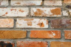 The wall is red brick, old, dirty, with peeling plaster. Dilapidated facade of the building with damaged plaster. Abstract banner. Brickwork close-up stock photography