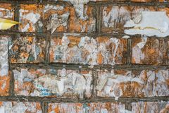 Brick wall with torn paper from ads. Wall of red brick with remains of ads stock photography