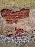 Wall with red brick visible through cracks. Photo wall with red brick visible through cracks, the facade of the old building in the afternoon, beige wall stock photos