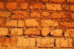 Wall of red earth bricks. Wall of a house in red clay, earth or soil bricks, great texture background, poverty, developing or tropical country concept Royalty Free Stock Photos