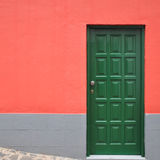 Wall of a red painted house with a green door Royalty Free Stock Photography