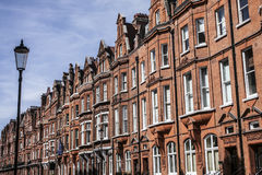 A wall of redbricked houses in London and the lamp post. This image shows a wall of redbrick houses in London. There`s a blue sky visible in the background Stock Photo