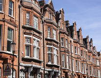 A wall of redbricked houses in London on a sunny day. This image shows a wall of redbrick houses in London Stock Images